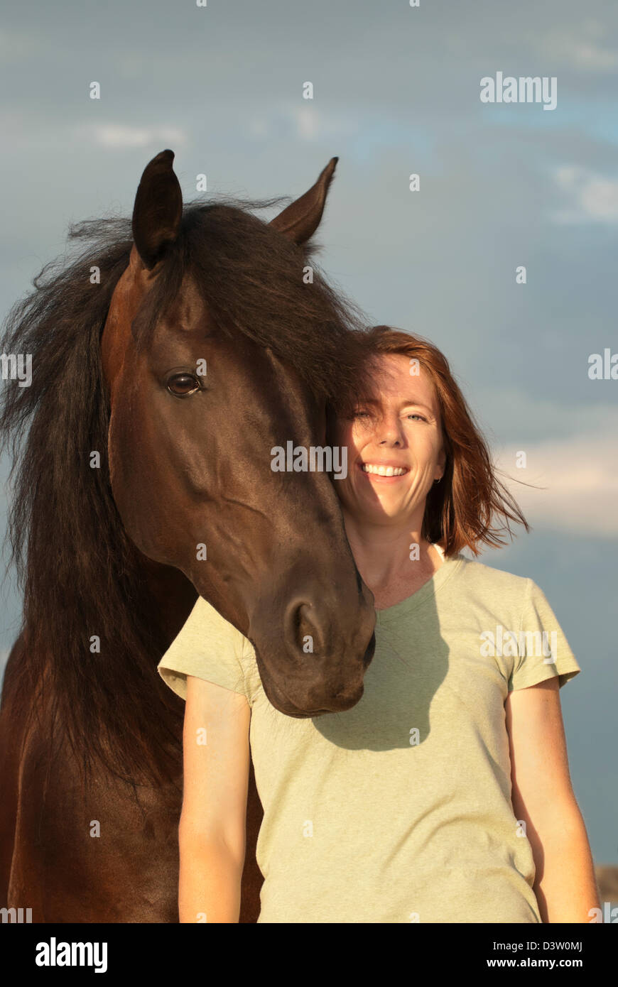 Woman horse trainer beside large black animal, smiling, happy, and confident horsewoman portrait in sunlight. - Stock Image