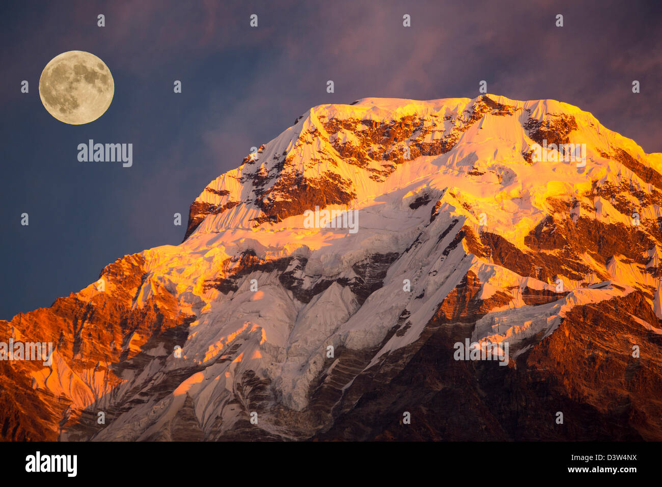 Alpenglow at sunrise on Annapurna South, Nepelese Himalayas, with a full moon. Stock Photo