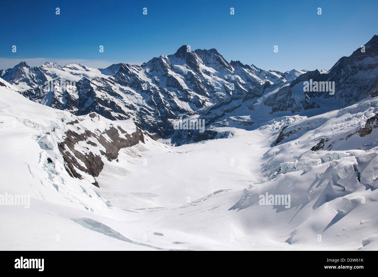 A view of snowcapped Swiss alpine mountain range seen from Eismeer tunnel station look-out point - Stock Image