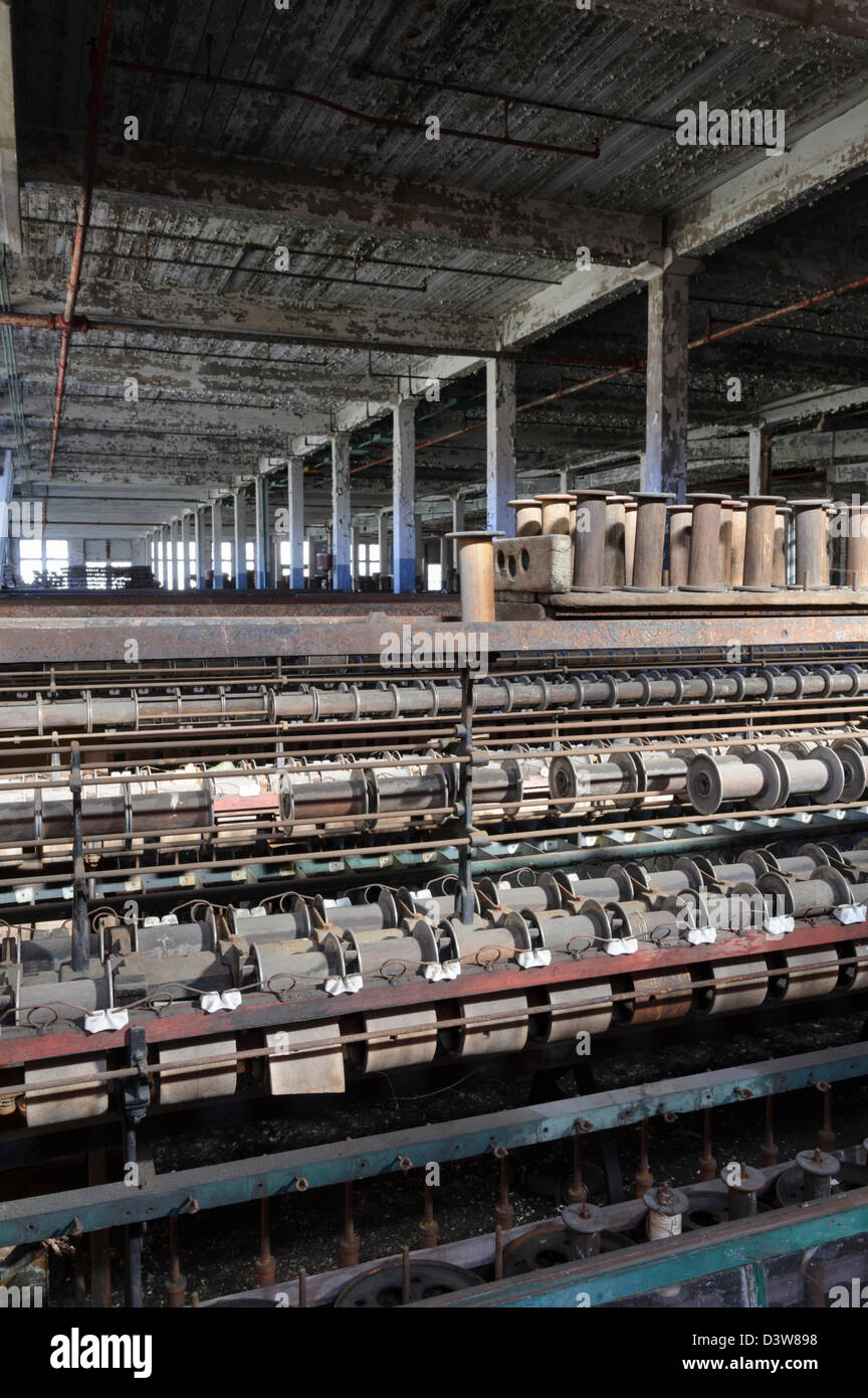 Textile mill weaving machinery sits stopped in an empty closed and abandoned American factory. - Stock Image
