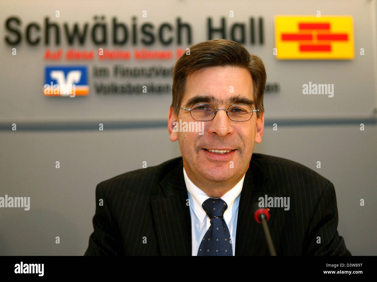 Matthias Metz, CEO of building society Schwaebisch Hall, pictured under the logo of his company at a press conference - Stock Image