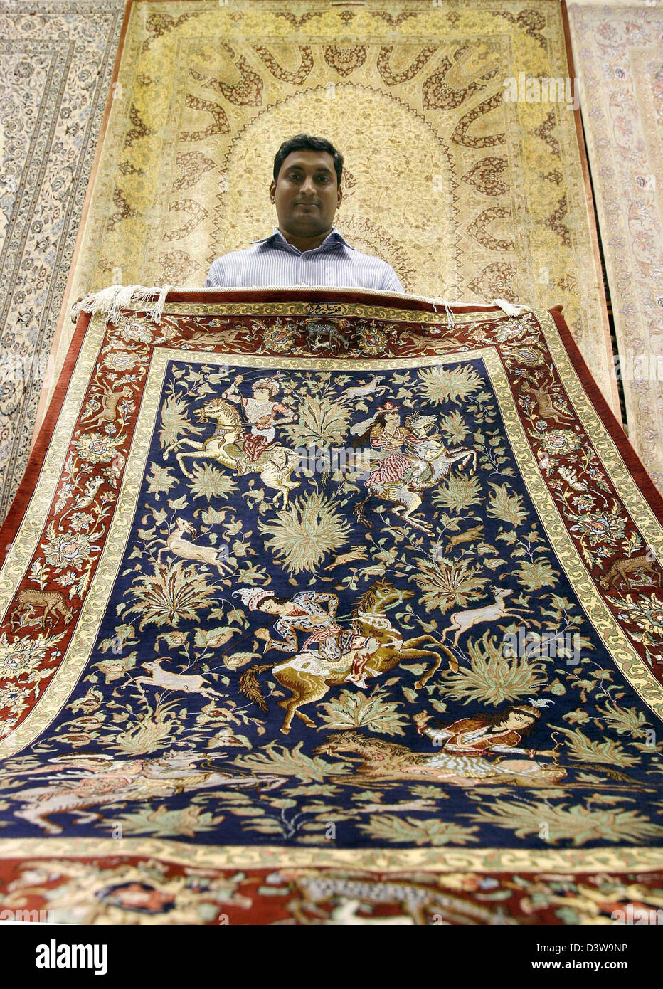 Mosharraf, the owner of 'Persian Carpet House', shows a carpet from his wide variety in his carpet shop at the Madinat Jumeirah Shopping-Center in Dubai, ...