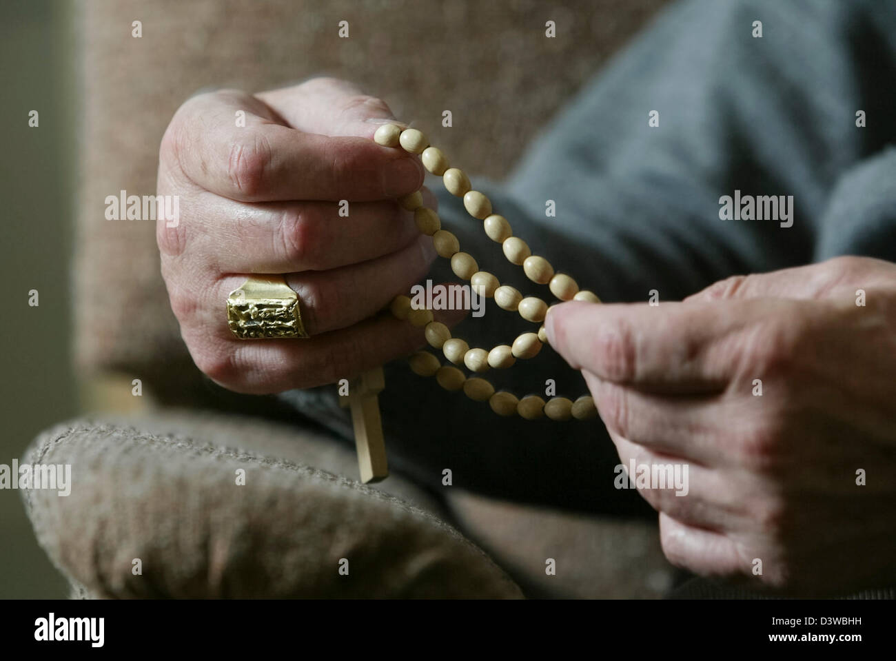 The hands of Cardinal Keith O'Brien, the most senior Roman Catholic cleric in Scotland, holding rosary beads - Stock Image