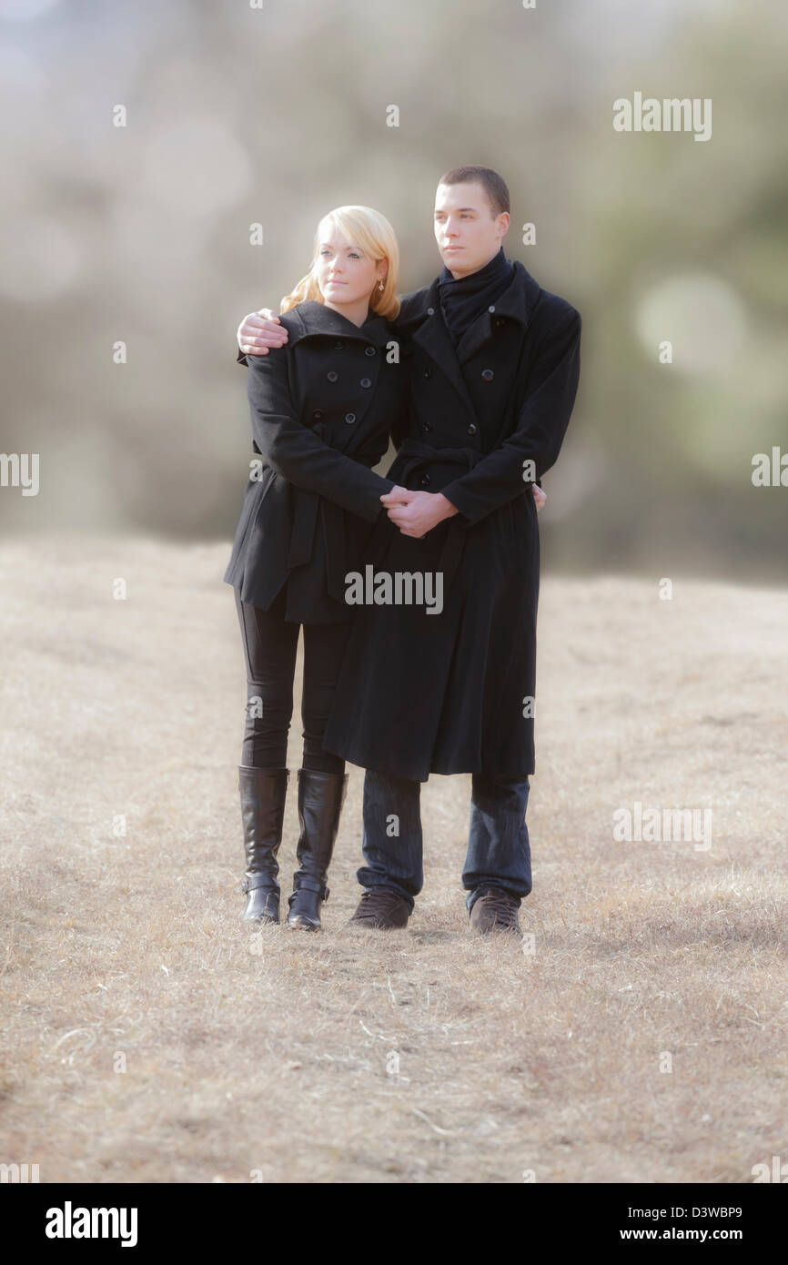 a couple in black clothes is walking in a meadow - Stock Image