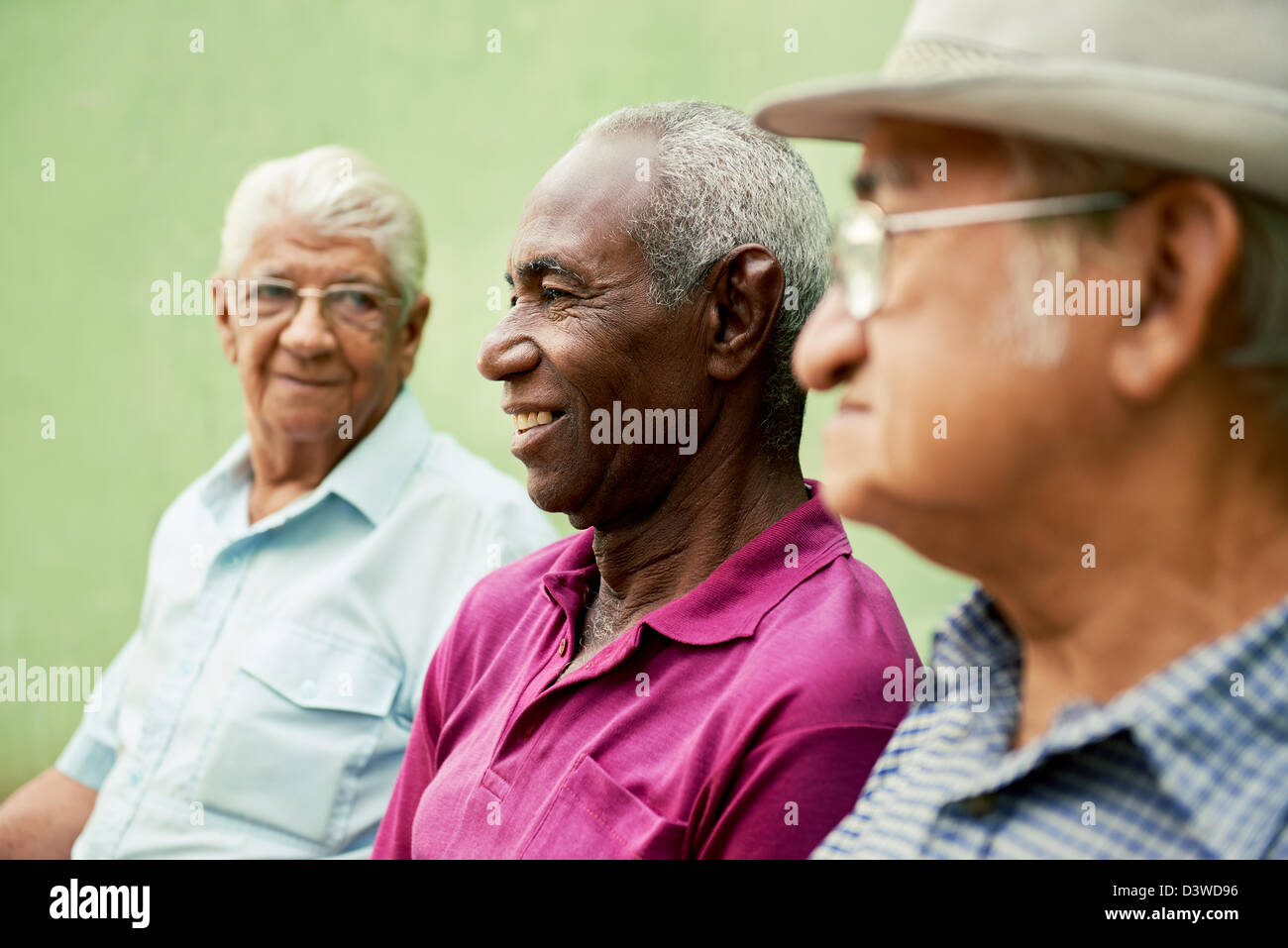 three senior men sitting on bench in park and talking - Stock Image