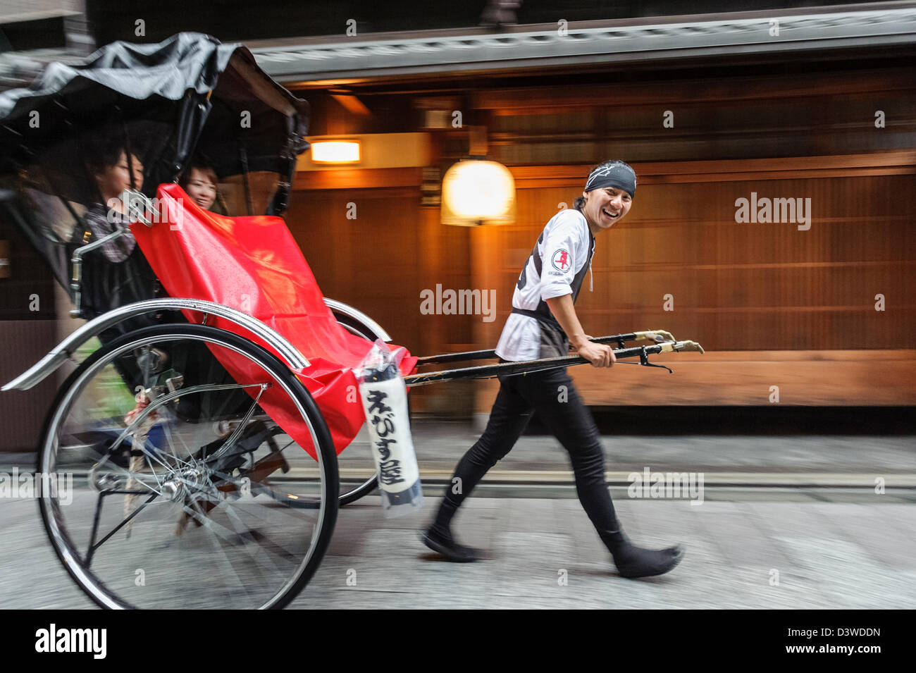 Man pulling a rickshaw in front of a temple, Kyoto, Japan, Asia - Stock Image