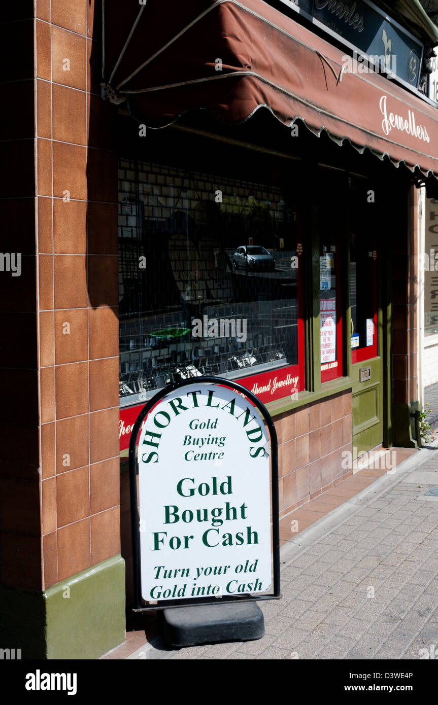 'Gold Bought For Cash' sign outside a jeweller's shop in south London. - Stock Image