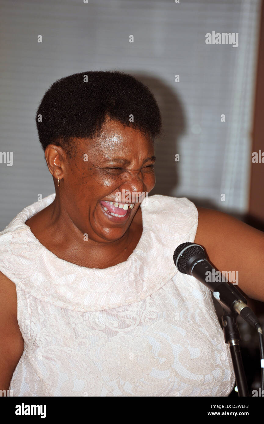 A woman laughing hard while giving a speech at a South African wedding. - Stock Image