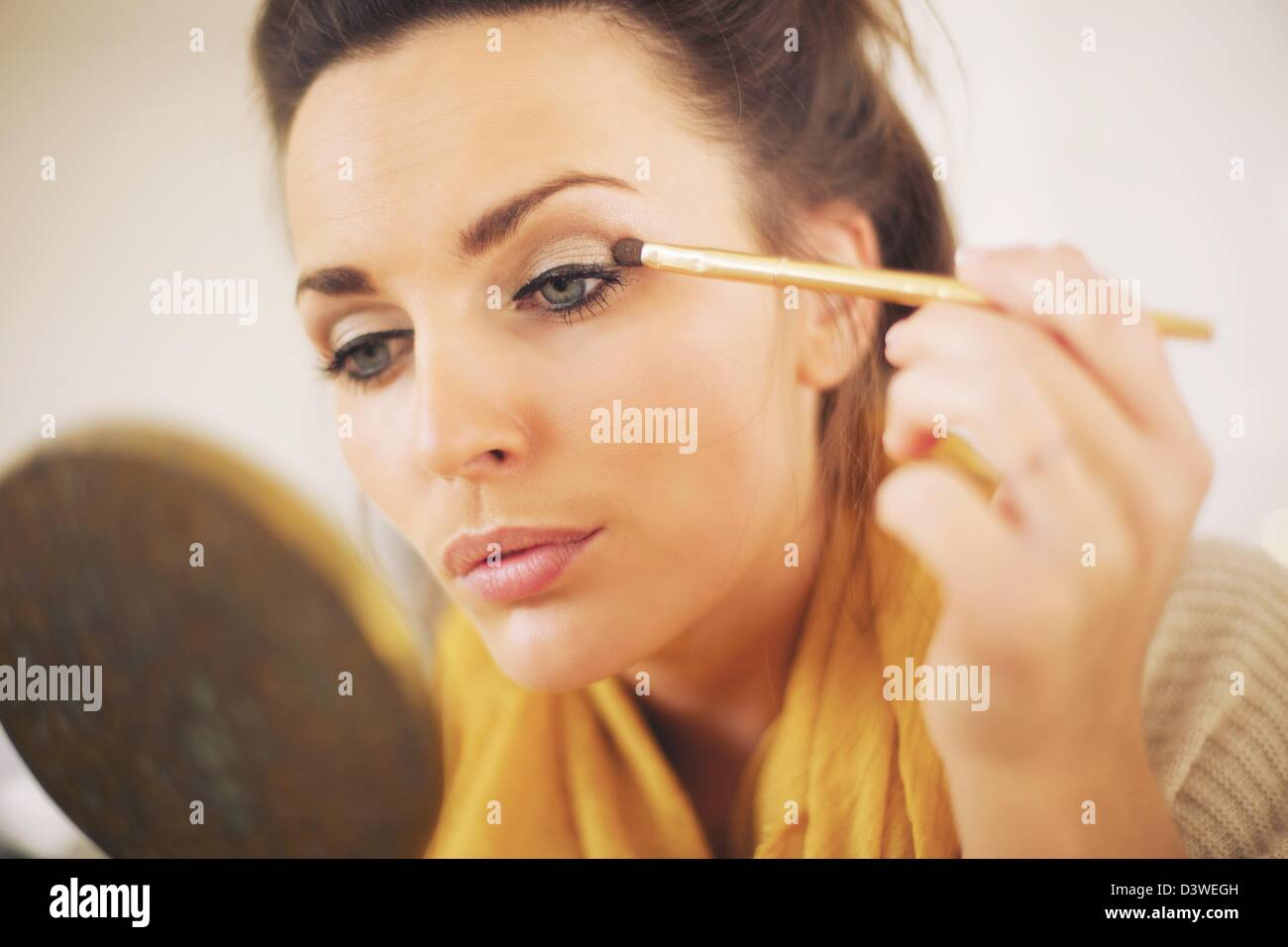 Attractive woman applying makeup while looking at the mirror - Stock Image