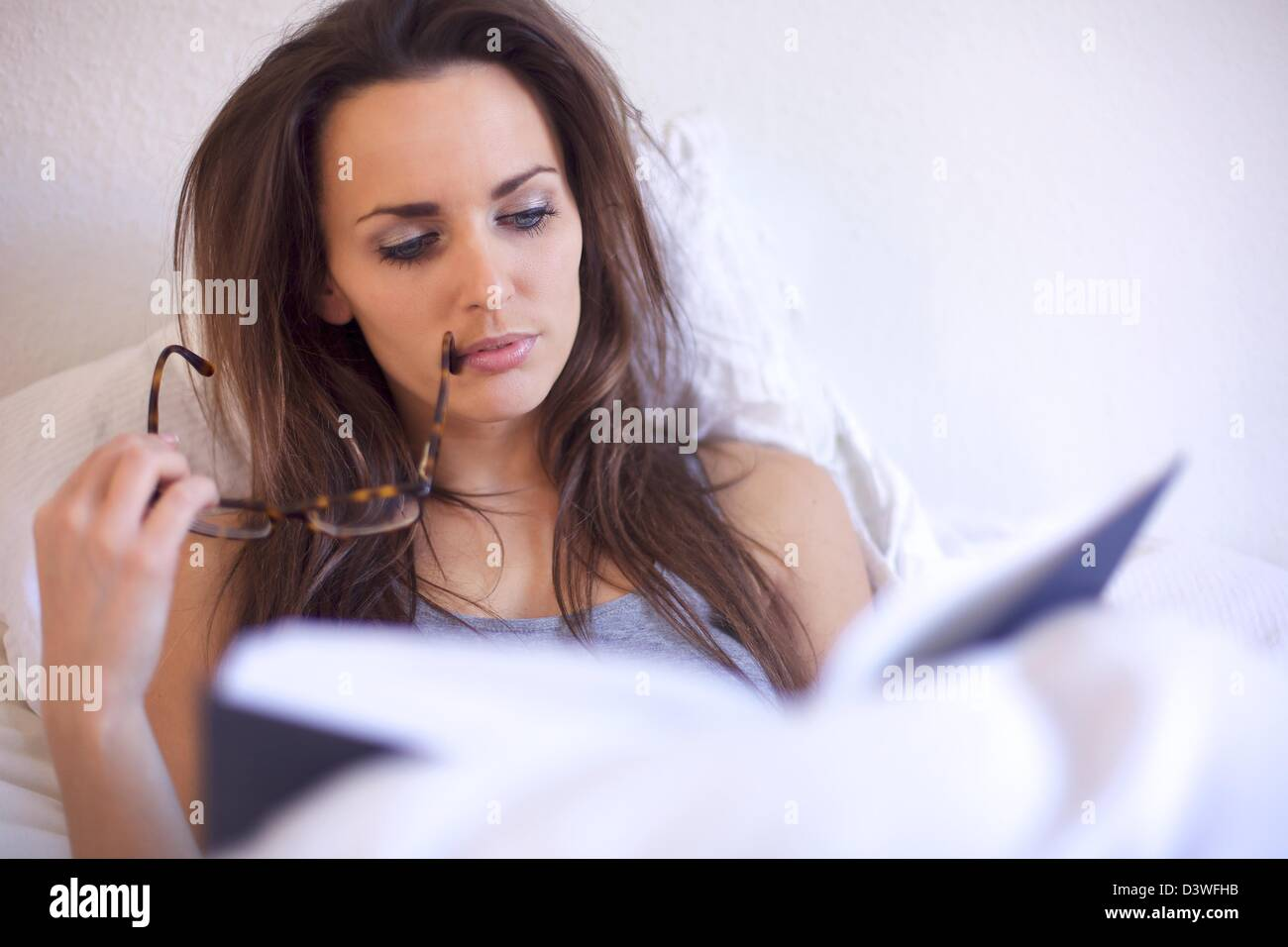 Brunette woman engrossed in reading a book while in her room - Stock Image