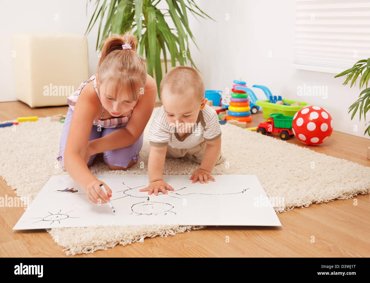 Brother watching his sister drawing on white sheet in the room - Stock Image