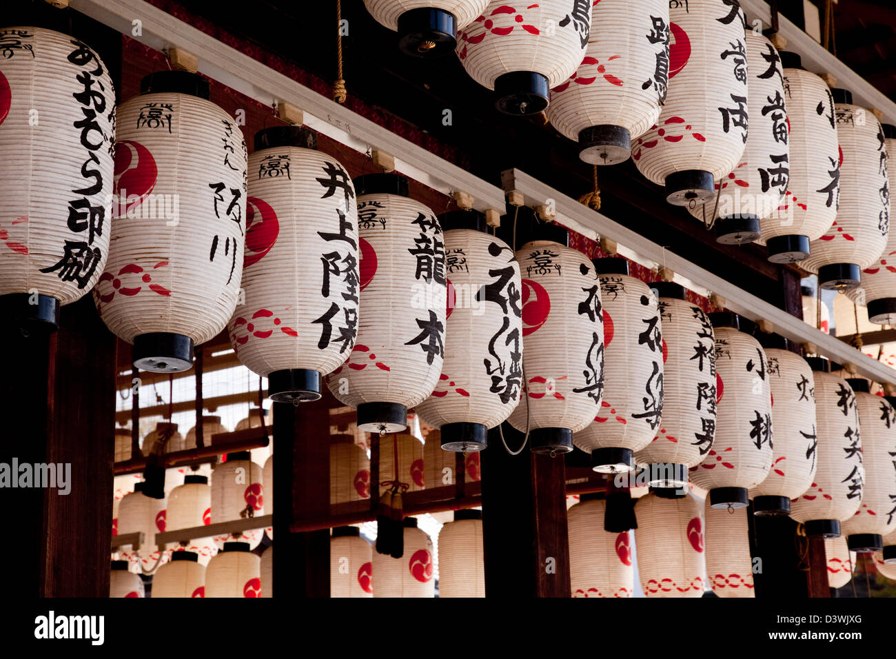 Japanese traditional paper lanterns, or chochin, in a Kyoto shrine often now lit by electricity and the plug points Stock Photo