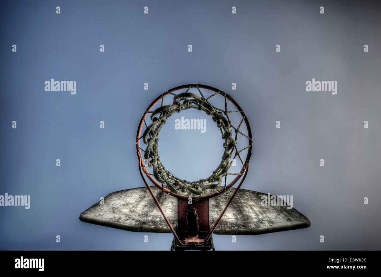 Looking up through a weathered outdoor basketball hoop - Stock Image