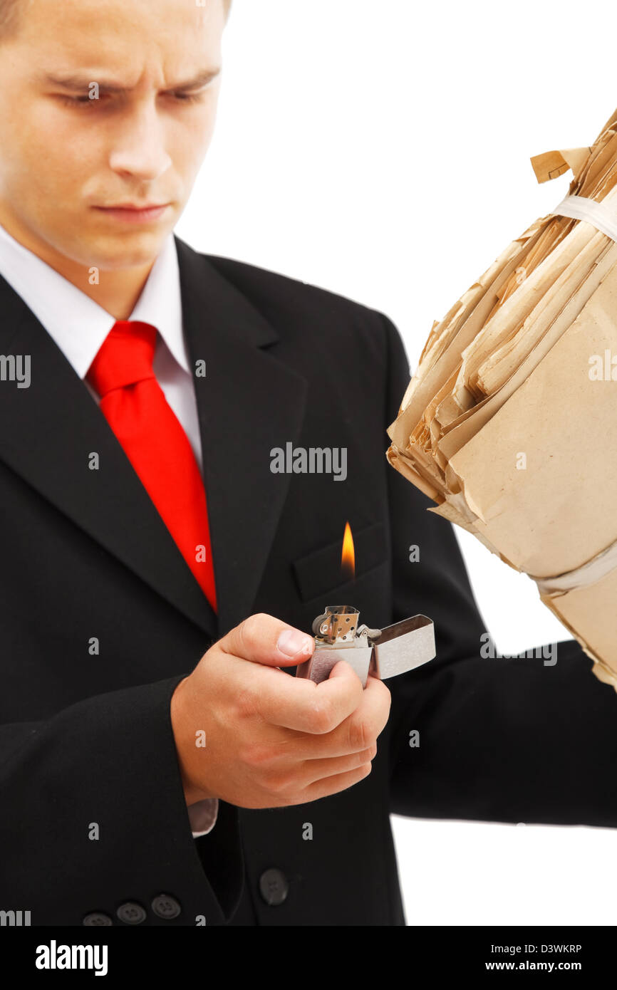 Young business man burning file folder with lighter, to destroy evidence, archive or other documents - Stock Image