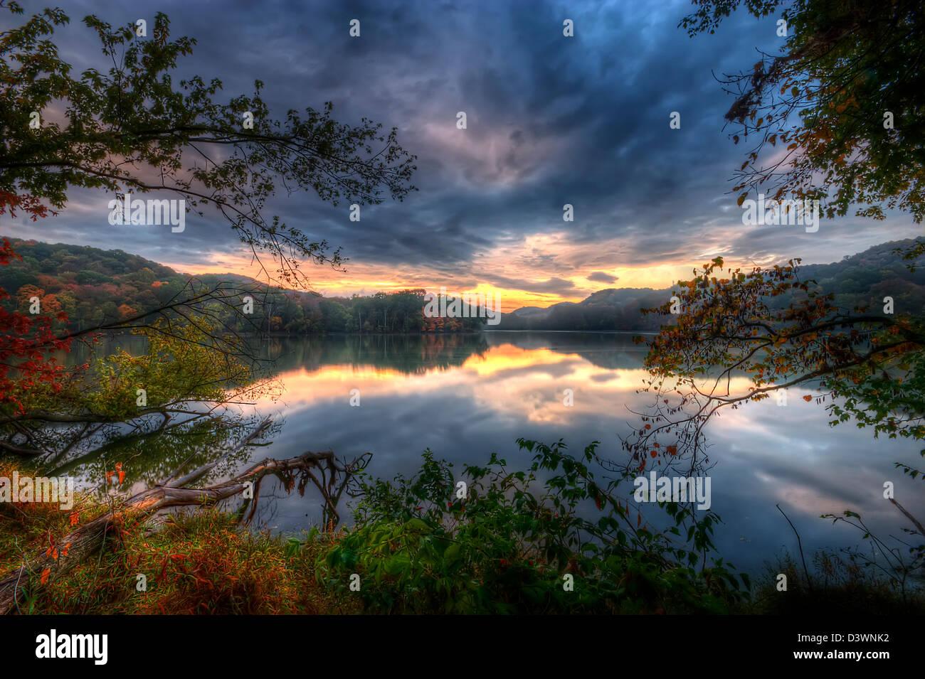 A beautiful sunrise over a lake - Stock Image