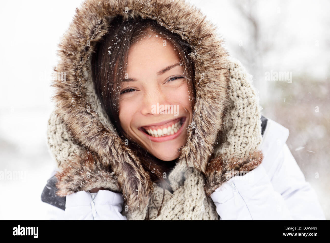 Closeup portrait of happy cheerful beautiful mixed race Caucasian Asian woman on snowing winter day - Stock Image
