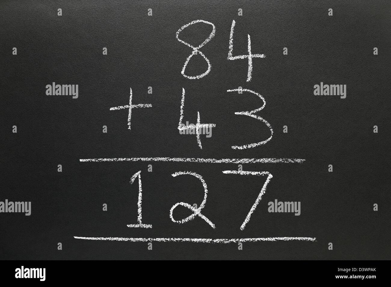 A basic addition sum written on a blackboard. - Stock Image