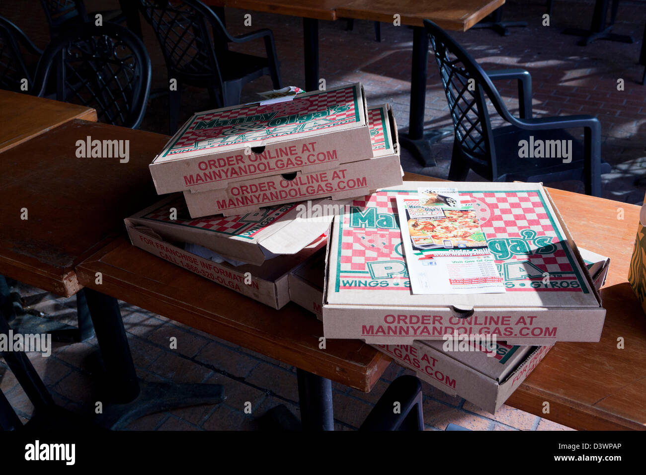 Empty pizza boxes on table - Stock Image