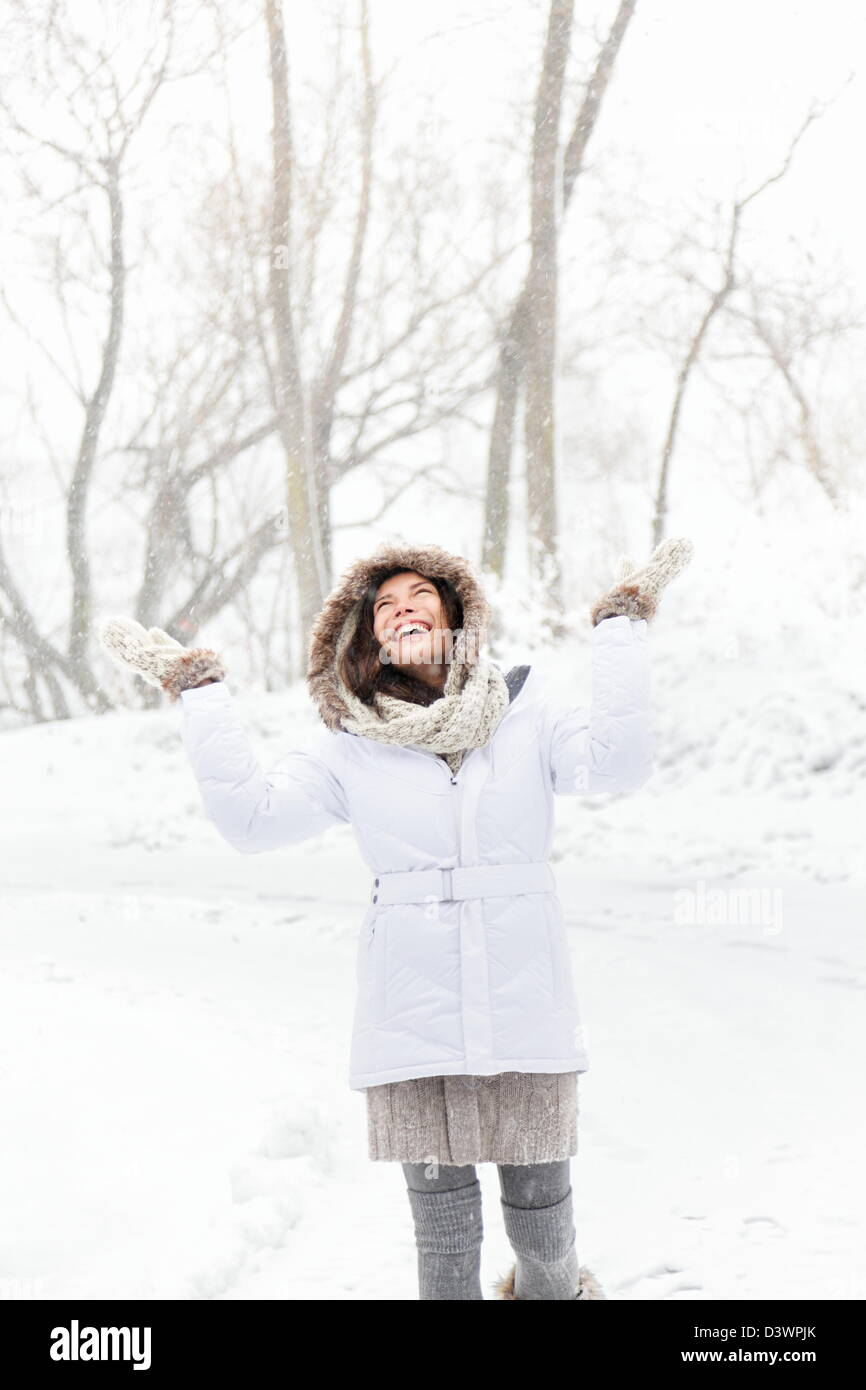 Smiling happy and joyful multicultural Asian Caucasian young woman playing in snow on snowing winter day - Stock Image