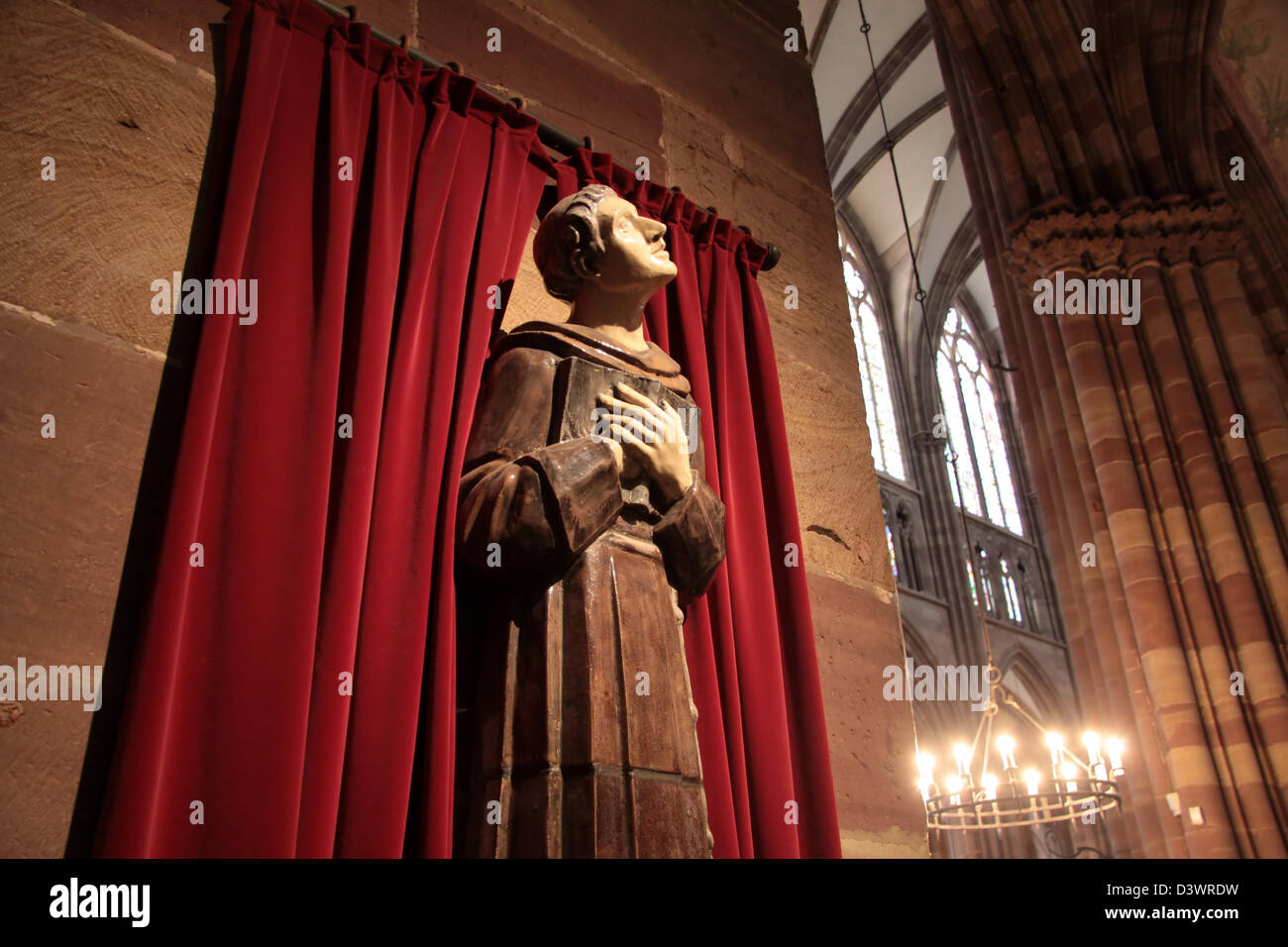Praying monk with red drop curtain in Strasbourg, Alsace, France Stock Photo