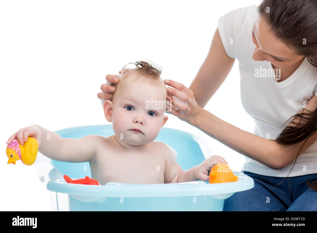 mother washing her baby girl in the bathtub with foam - Stock Image