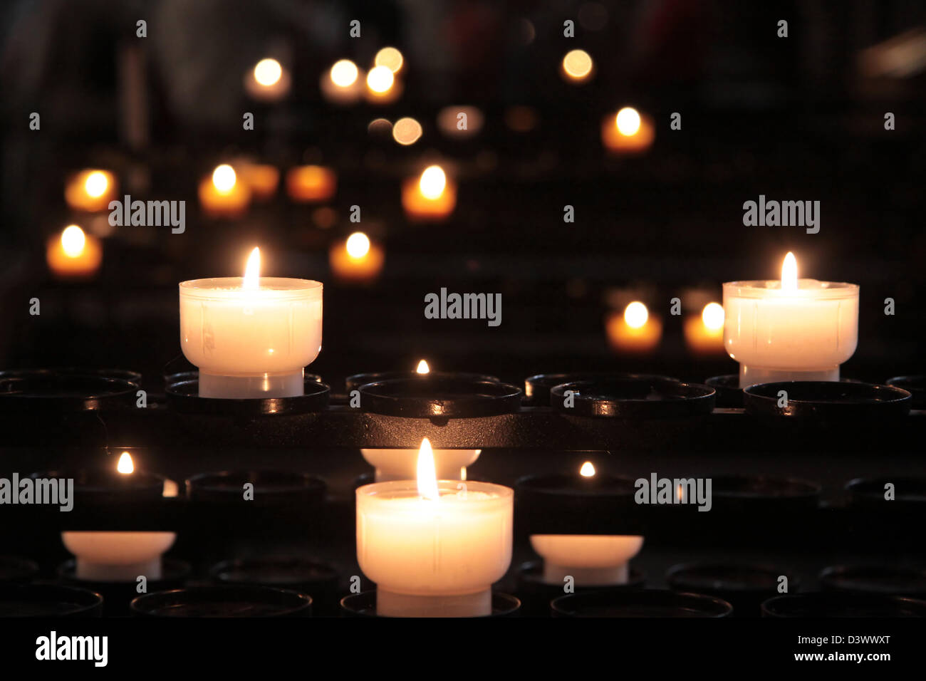 Blazing candle-flames in the Strasbourg cathedral Alsace, France - Stock Image