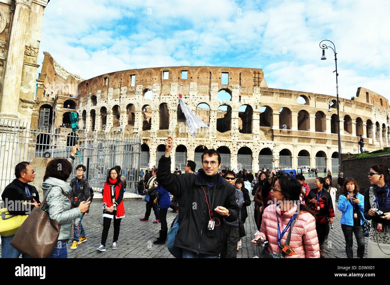Japanese Tourists are rounded up by a local guide, Colosseum, Rome Italy - Stock Image