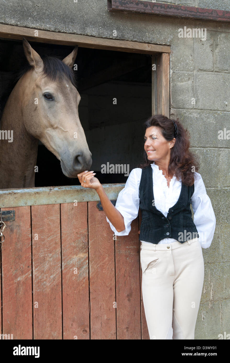 a mature woman in riding gear happily pets a horse in a cotswold