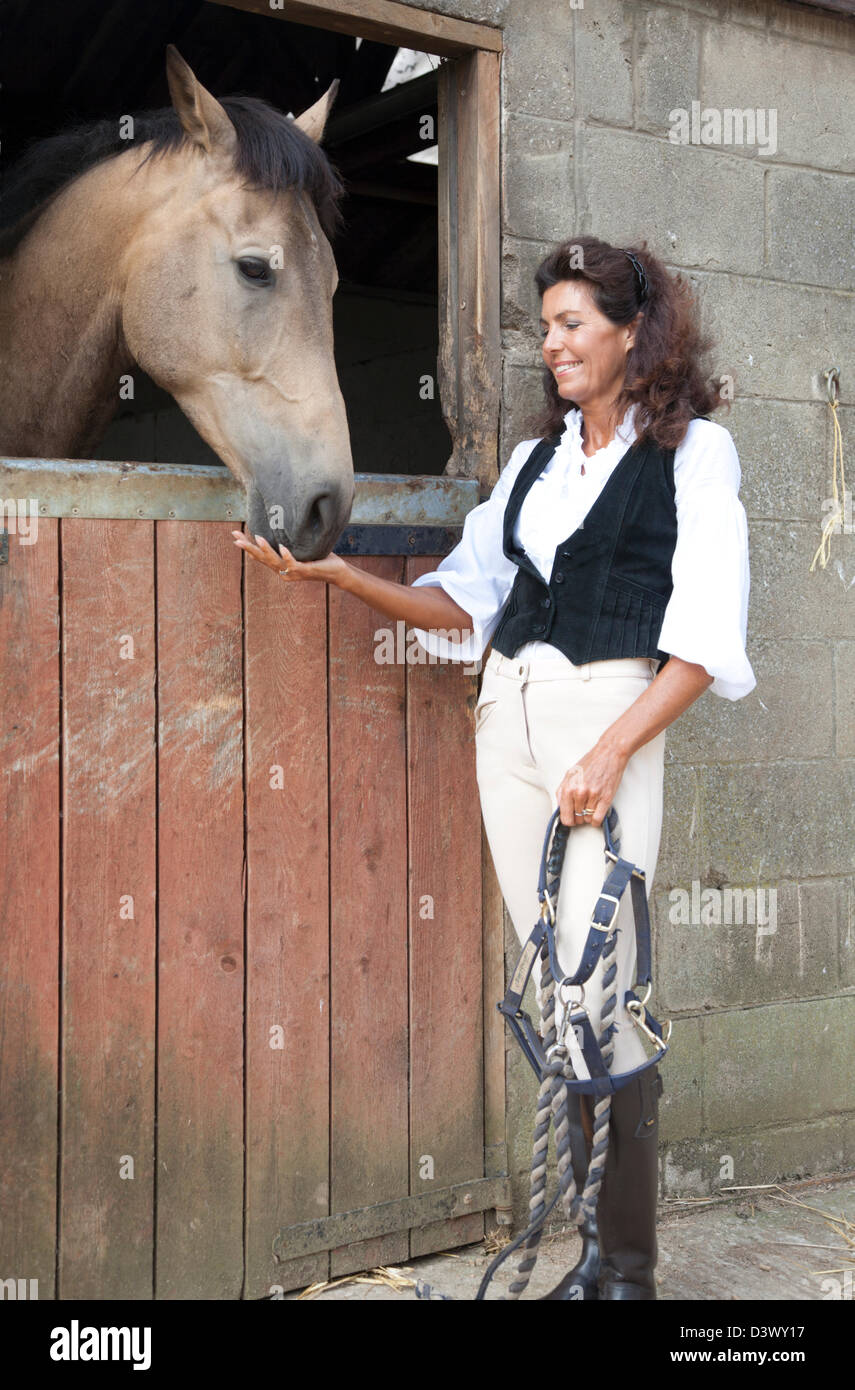 a mature woman in riding gear with tack happily pets a horse in a