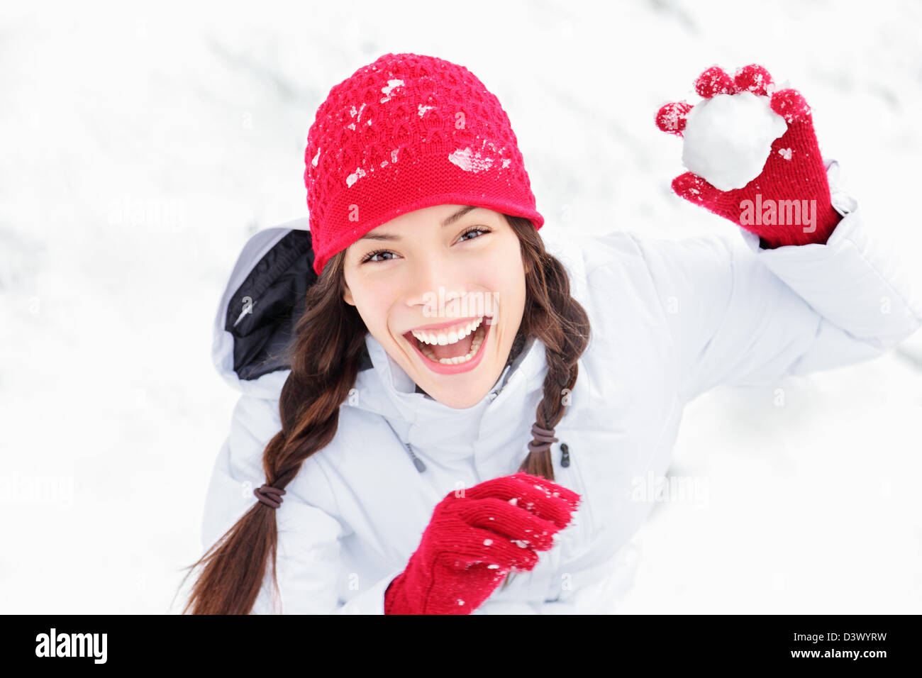 Cute playful multicultural Asian Caucasian young woman throwing snowball at camera having fun outdoors on snowing - Stock Image