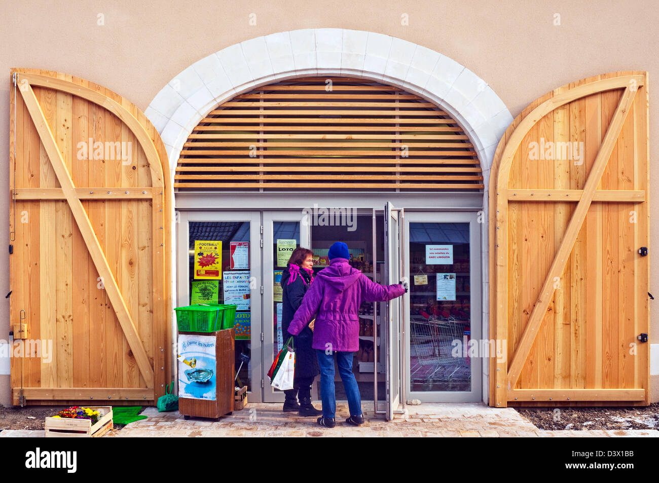 New arched wood double doors on shop frontage - France. - Stock Image