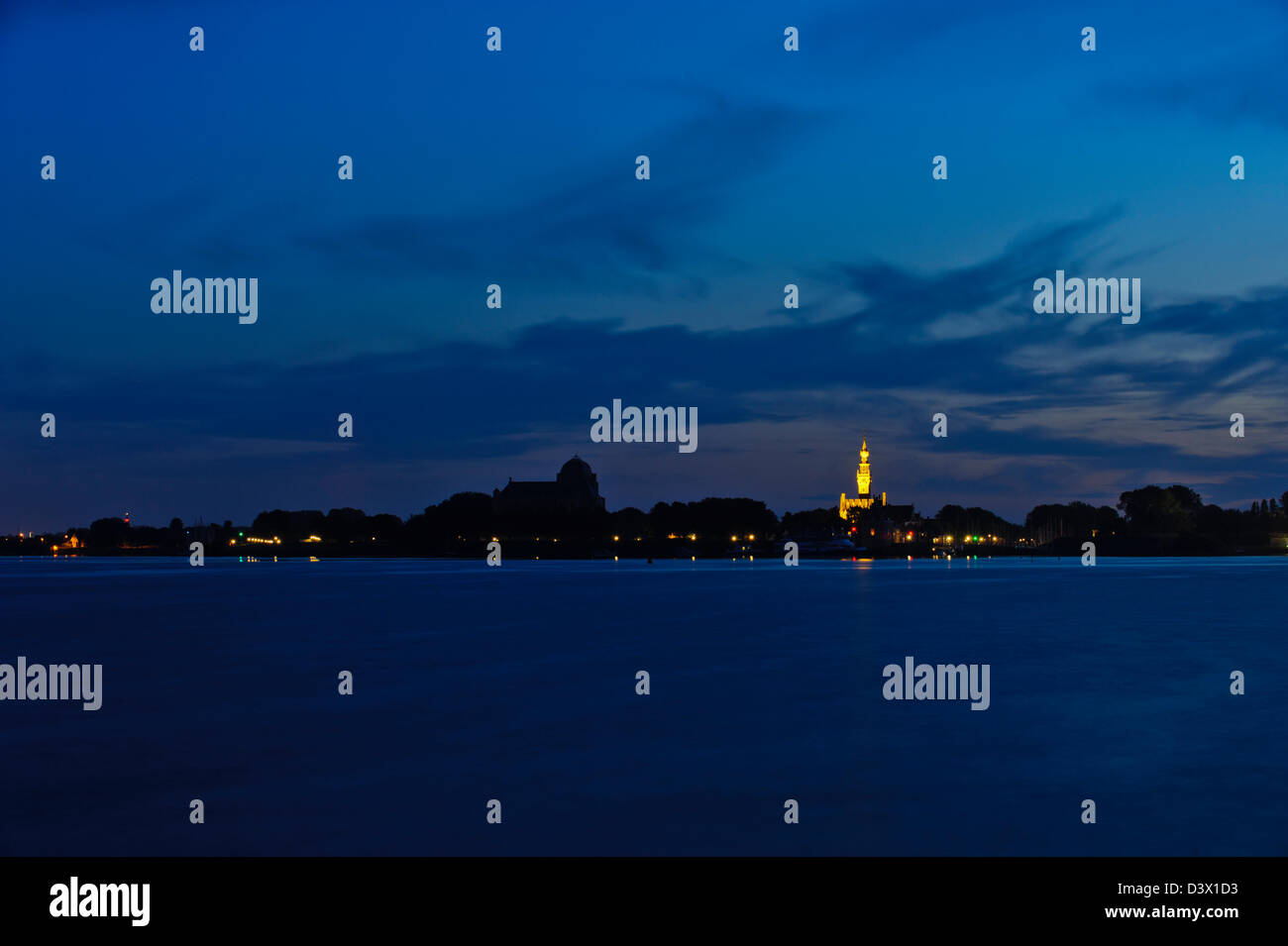 Dusk at  the Veerse Meer. Veere  with illuminated Town Hall on the background. Walcheren, Zeeland. Netherlands. - Stock Image