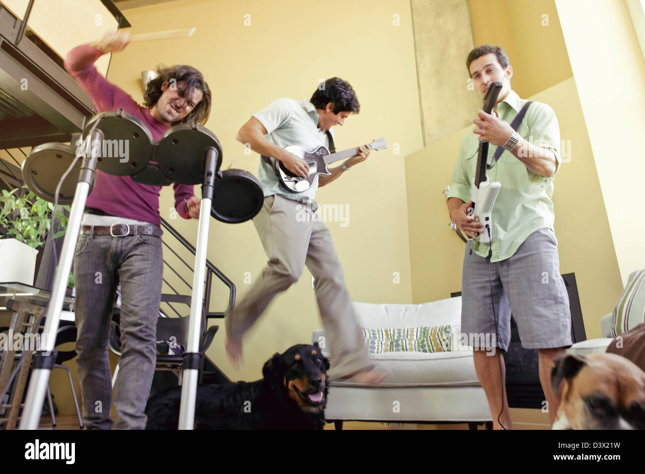 Mexian-American Men Friends Playing Rock Band Music Video Game - Stock Image