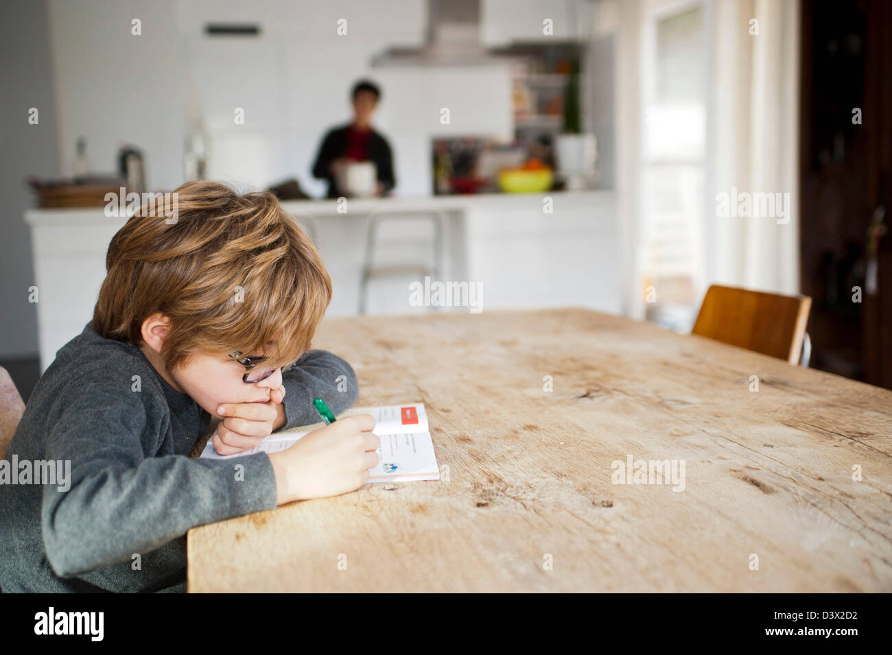 10 Year Old Boy Is Doing Homework At The Kitchen Table In A Modern House,  He Wears Glasses.