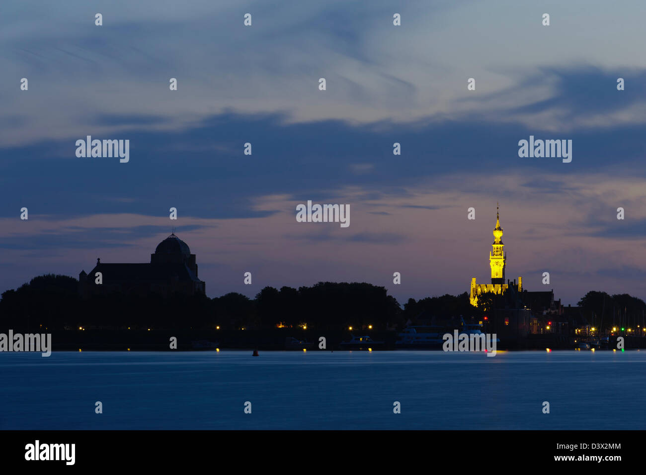 sunset at  the Veerse Meer. Veere  with illuminated Town Hall on the background. Walcheren, Zeeland. Netherlands. - Stock Image