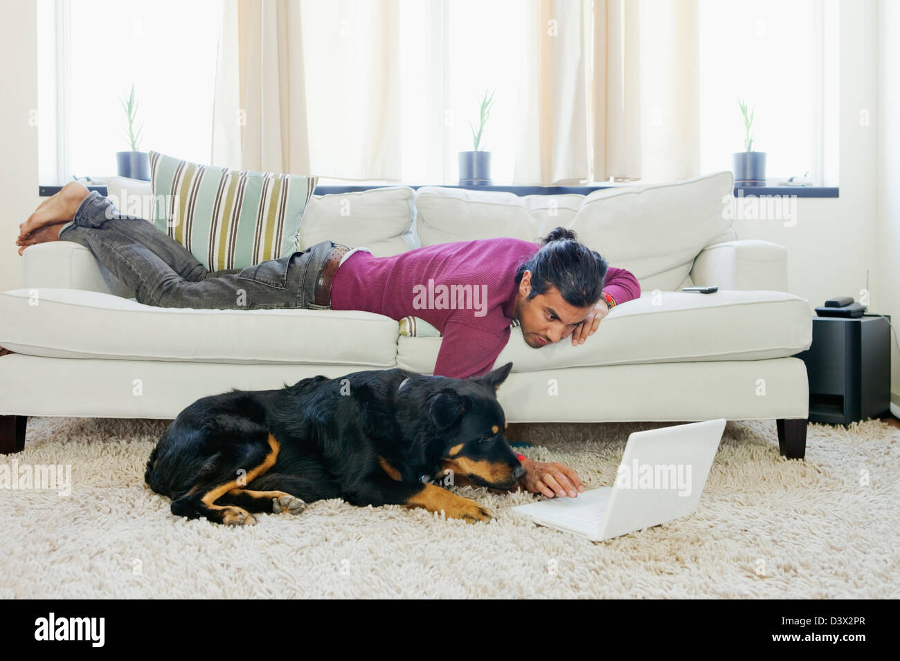 A young casual Hispanic-Latino man entertaining his pet dog by surfing internet using laptop - Stock Image