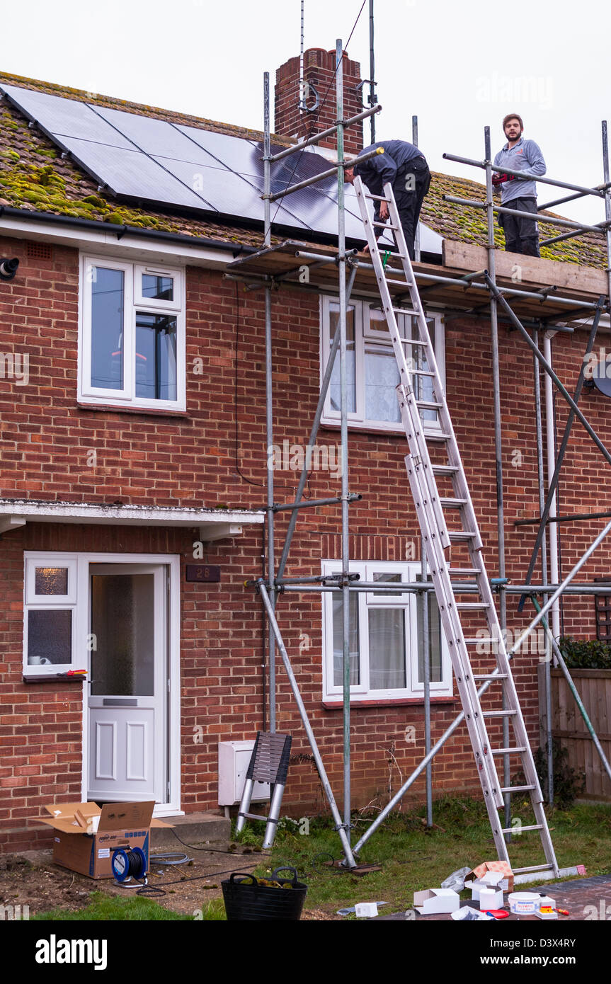 Two men fitting solar panels on the roof of a house in the Uk - Stock Image