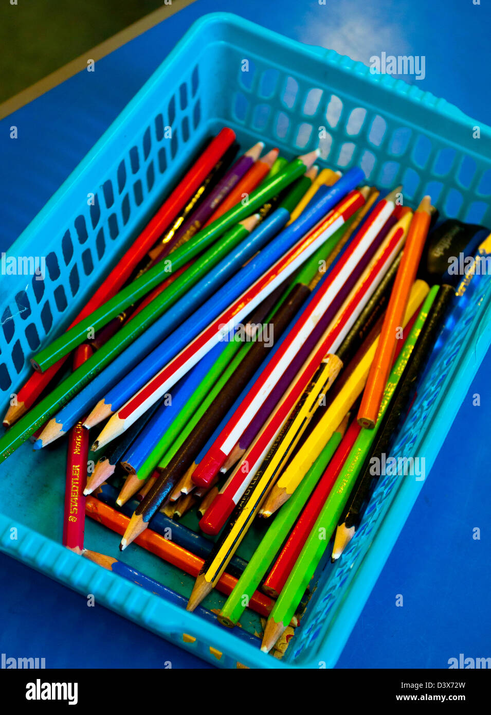 Close up view of colourful pencils in a plastic basket in a school classroom Stock Photo