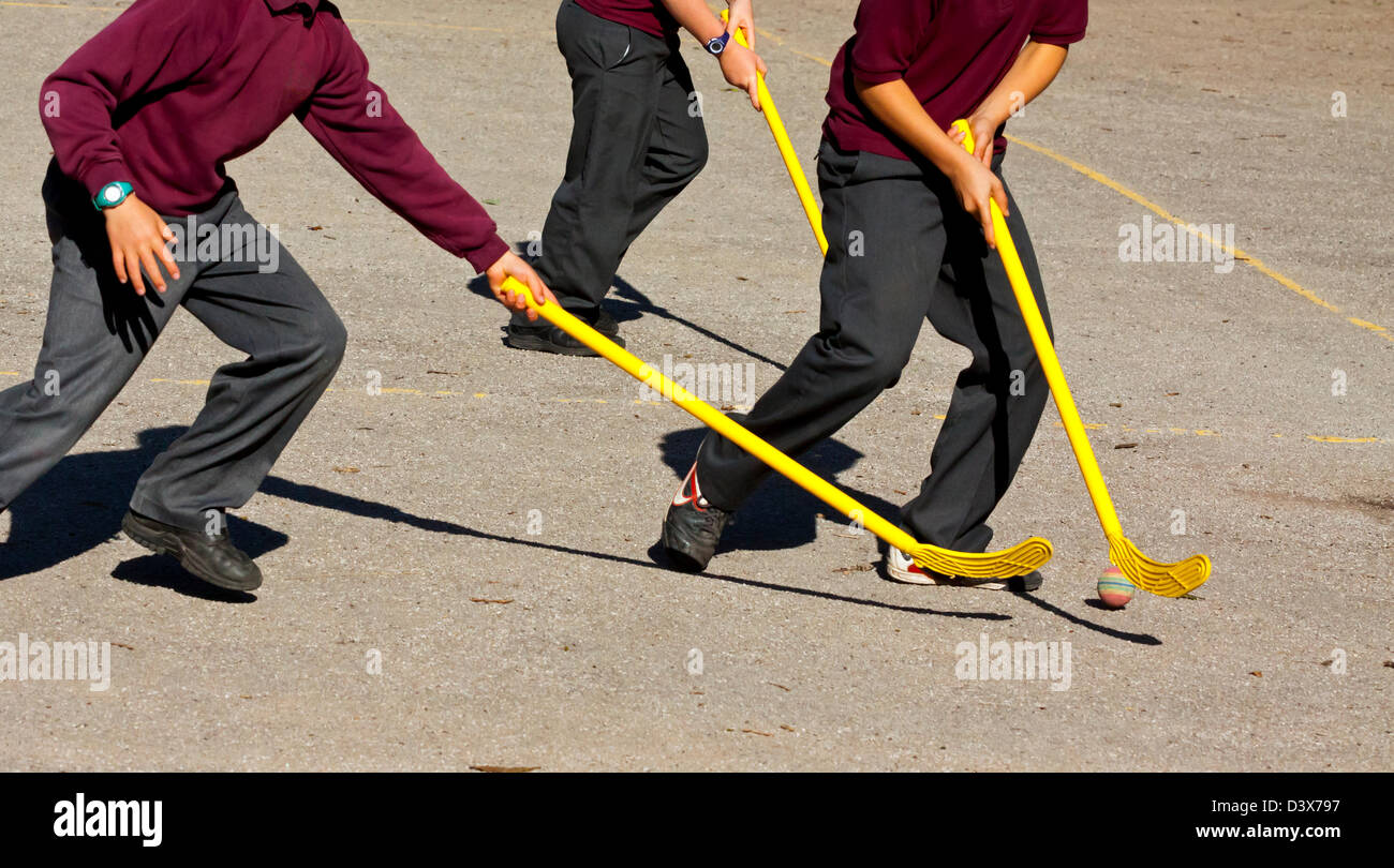 Detail of primary school children playing hockey in a school playground - Stock Image