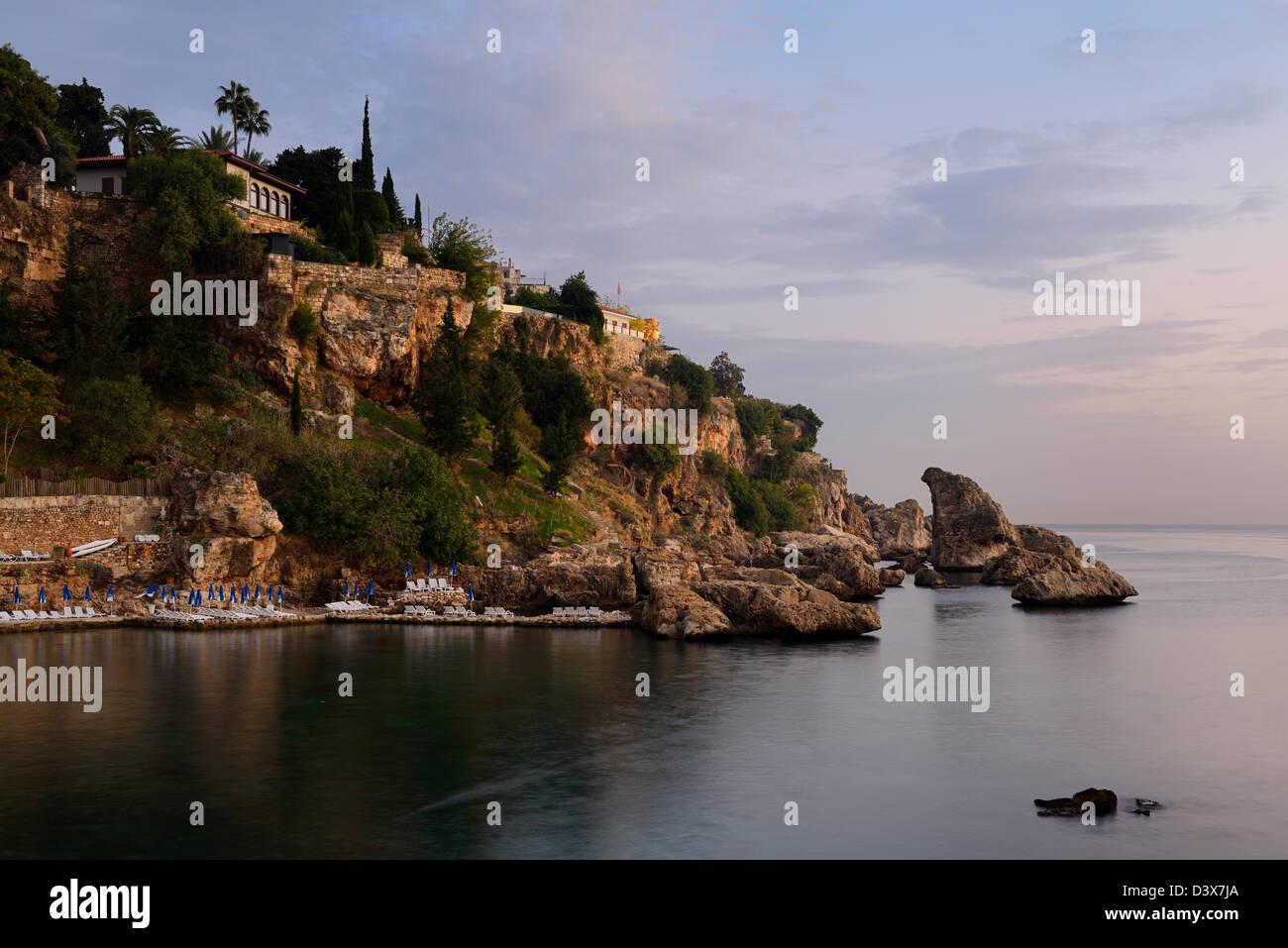 Cliffside resort at dusk on Turkish Riviera at Antalya Kaleici Harbour Turkey - Stock Image