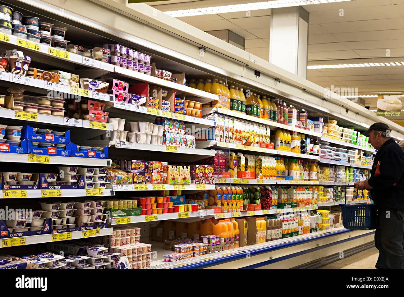 Man shopping in Tesco in front of cooled shelves of orange juice and dairy products, UK - Stock Image