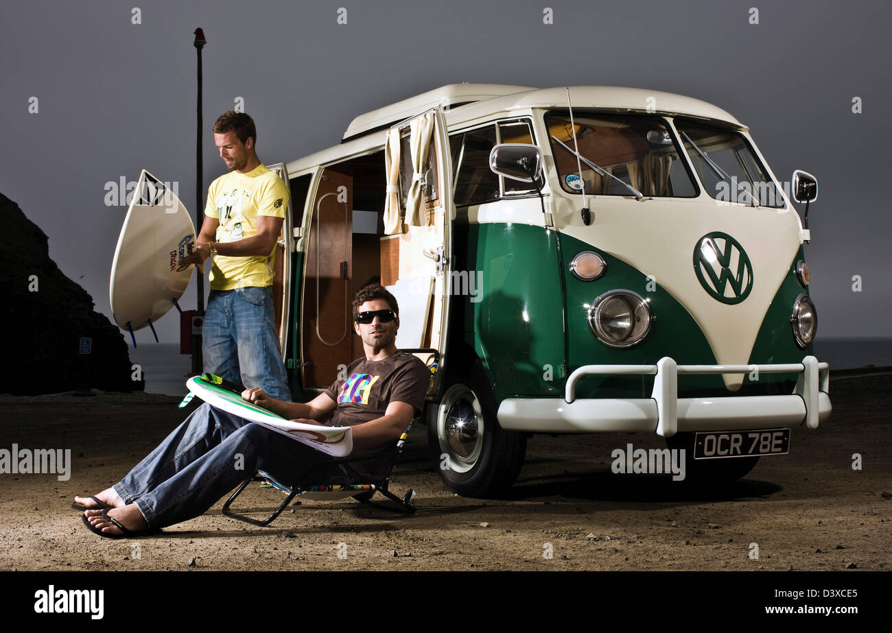 Surfers unloading boards from VW campervan, St Agnes, Cornwall, UK - Stock Image