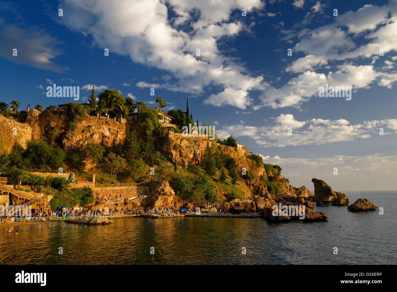 Cliffside resort and beach on Turkish Riviera at Antalya Kaleici Harbour Turkey at sunset - Stock Image