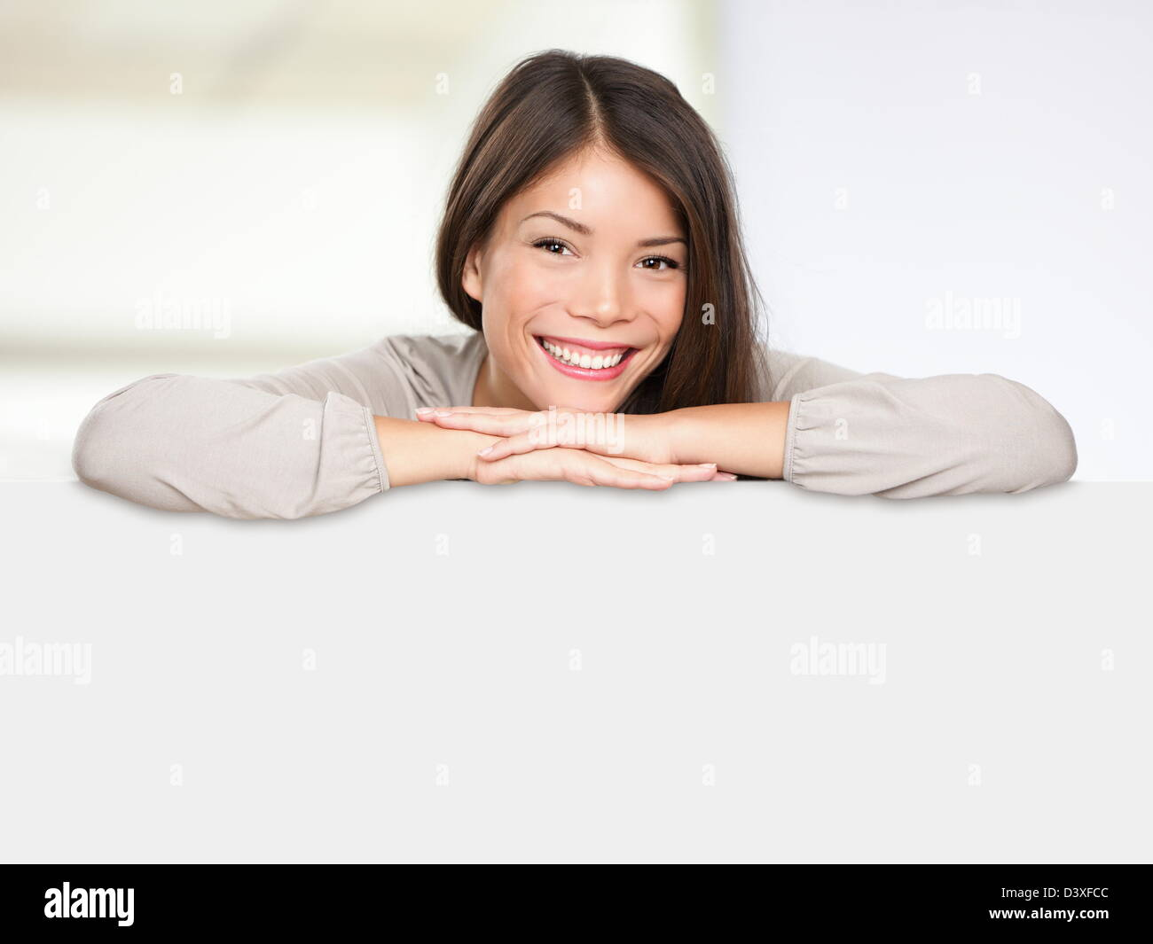 Relaxed Multiethnic mixed race Asian and Caucasian woman wearing casual  leaning on blank billboard sign - Stock Image