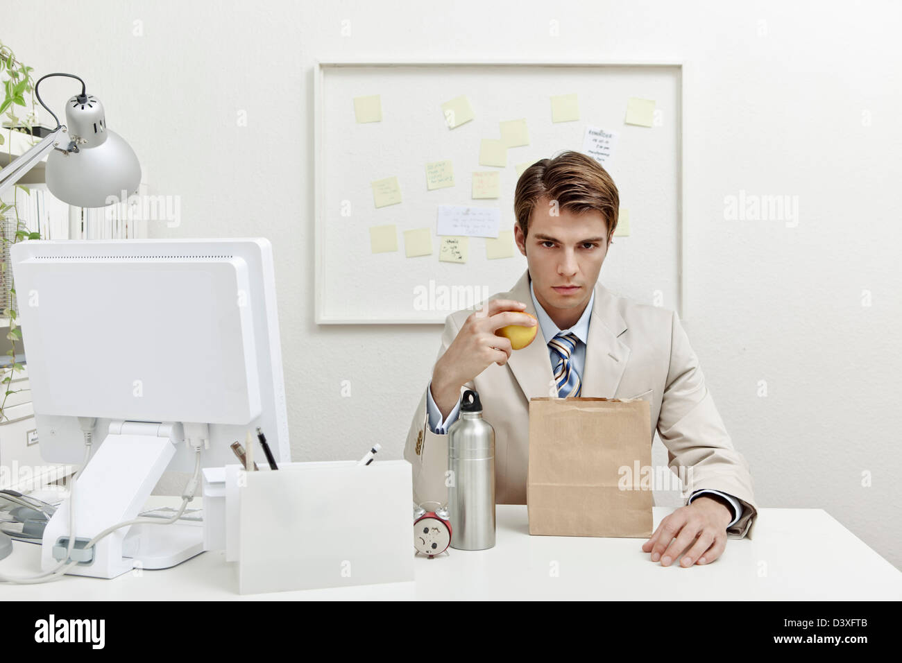 A concept photo of a young office worker trying to save money by bringing lunch to work. - Stock Image