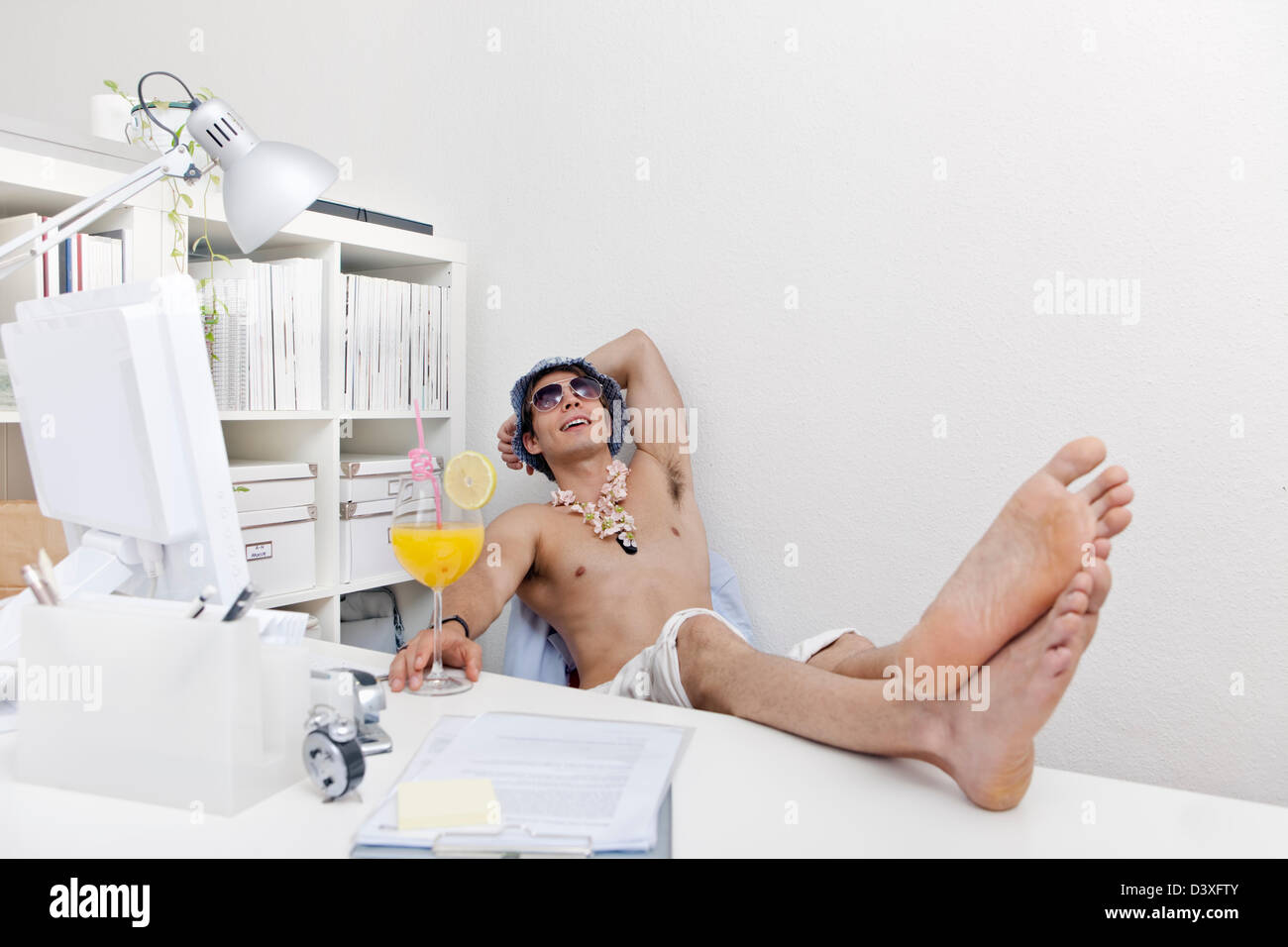 young man in beachwear and sunglasses and and lei (garland) with cocktail drink at work. in holiday mood. - Stock Image