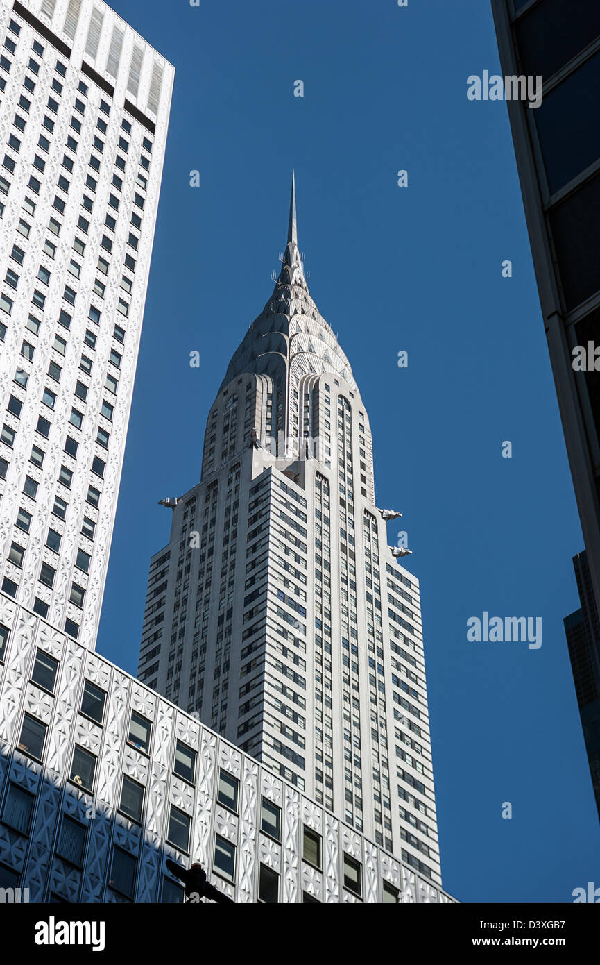Looking up from street level at New York's Chrysler Building between nearby skyscrapers. - Stock Image