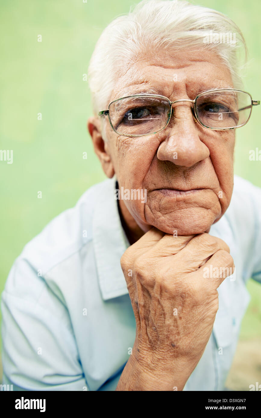 people and emotions, portrait of depressed senior hispanic man with glasses looking at camera, leaning with hands - Stock Image