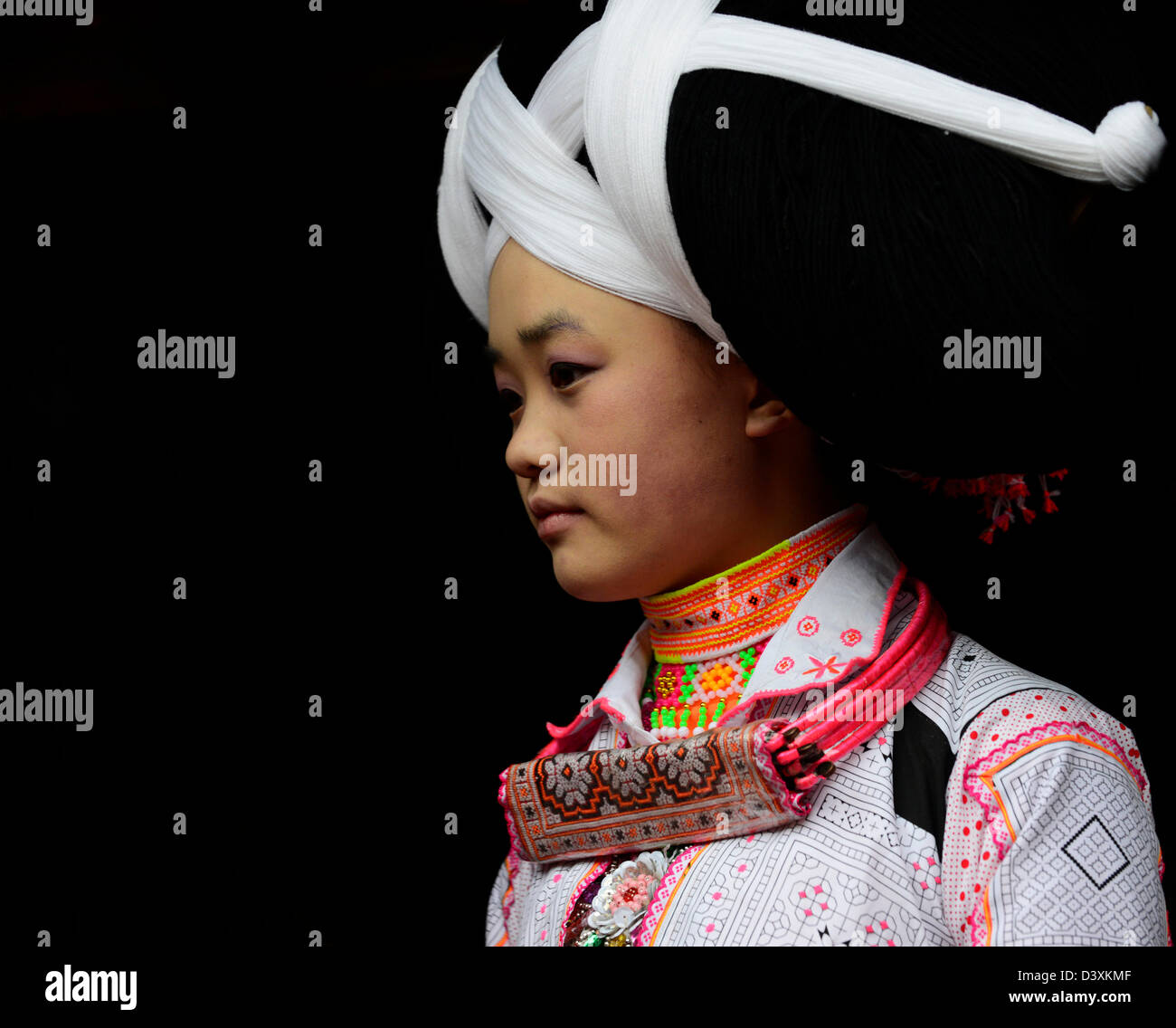 A Long Horn Miao teenage girl getting ready for the Tiao Hua festival in Guizhou. - Stock Image