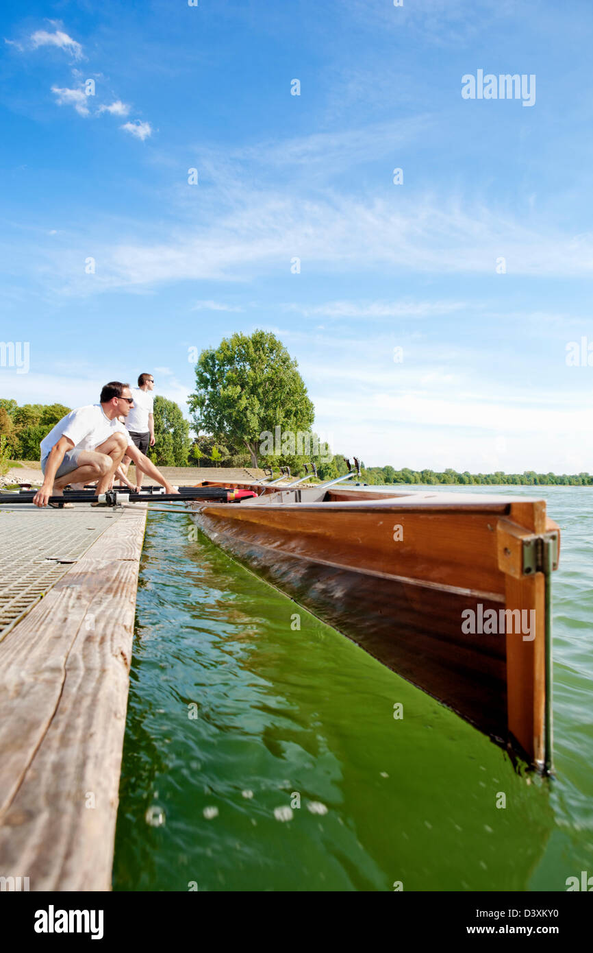 Teamwork Concept of Men Rowing Team Setting Paddles and Boat - Stock Image